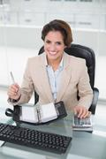 Stock Photo of Businesswoman using calculator and diary smiling at camera