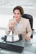 Smiling businesswoman using calculator and diary looking at camera Stock Photos
