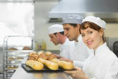 Happy female baker smiling at the camera - stock photo