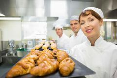 Stock Photo of Three young bakers standing in a bakery