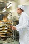 Handsome young baker pushing a trolley - stock photo