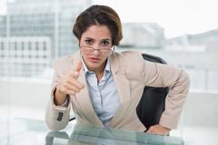 Irritated businesswoman looking at camera - stock photo