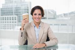 Smiling businesswoman holding disposable cup at her desk - stock photo