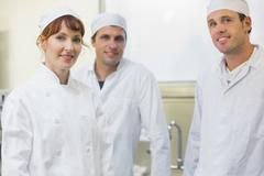 Three bakers posing in a kitchen Stock Photos