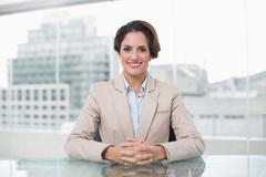 Content businesswoman looking at camera at her desk - stock photo