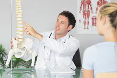 Stock Photo of Handsome doctor showing a patient something on skeleton model