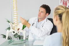 Content doctor showing a patient something on skeleton model - stock photo