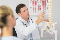 Good looking doctor showing a patient something on skeleton model Stock Photos