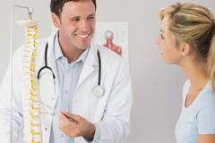 Lucky doctor showing a patient something on skeleton model - stock photo