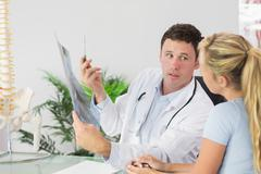 Serious doctor showing a patient something on x-ray - stock photo