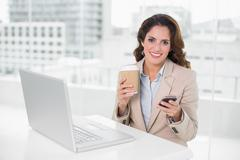 Cheerful businesswoman holding disposable cup and smartphone - stock photo