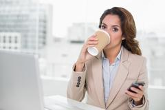 Attractive businesswoman drinking from disposable cup - stock photo