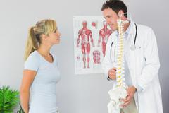 Stock Photo of Content doctor holding skeleton and talking to patient