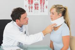 Stock Photo of Attractive doctor examining neck of a patient