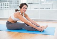 Sporty smiling brunette stretching - stock photo