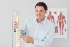 Stock Photo of Handsome smiling doctor pointing at skeleton model