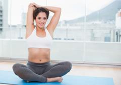 Sporty pleased brunette stretching on exercise mat Stock Photos