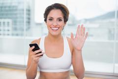 Stock Photo of Sporty cheerful brunette waving