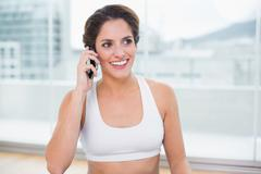 Stock Photo of Sporty smiling brunette phoning