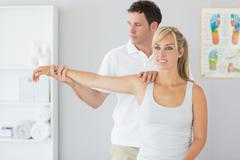 Handsome physiotherapist examining patients arm - stock photo