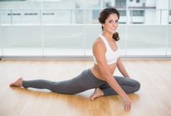 Sporty cheery brunette stretching on the floor Stock Photos
