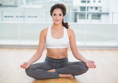 Sporty content brunette sitting in lotus pose - stock photo