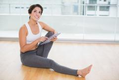 Sporty thoughtful brunette using tablet sitting on the floor - stock photo