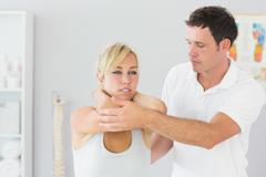 Handsome physiotherapist examining patients back - stock photo
