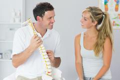 Smiling physiotherapist showing patient something on skeleton model - stock photo