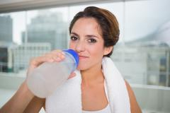 Sporty content brunette holding water bottle Stock Photos