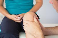 Stock Photo of Physiotherapist checking patients knee