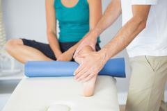 Physiotherapist checking patients leg Stock Photos