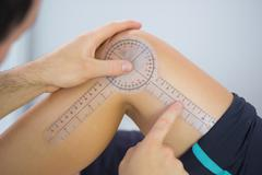 Physiotherapist examining knee angle with goniometer - stock photo