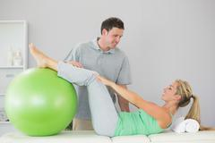 Stock Photo of Patient holding exercise ball with legs
