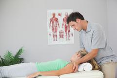 Stock Photo of Attractive physiotherapist massaging patients neck