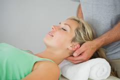 Physiotherapist massaging patients head - stock photo