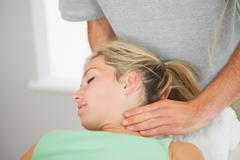 Stock Photo of Physiotherapist putting pressure to patients neck