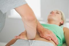 Physiotherapist checking patients pelvis alignment - stock photo
