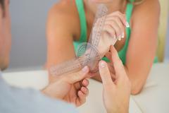 Physiotherapist examining patients wrist with goniometer - stock photo