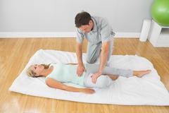 Physiotherapist treating patient on a mat on the floor Stock Photos