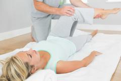 Stock Photo of Physiotherapist checking patients leg on a mat on the floor