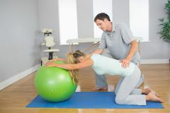 Physiotherapist controlling patient doing exercise with exercise ball - stock photo