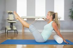 Blonde patient doing exercise on the floor - stock photo