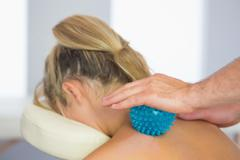 Physiotherapist massaging female patient with blue massage ball - stock photo