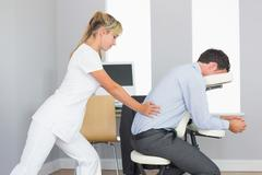 Masseuse treating clients lower back in massage chair Stock Photos