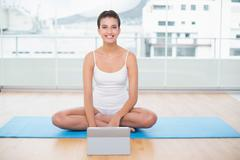 Smiling natural brown haired woman in white sportswear using a tablet pc - stock photo