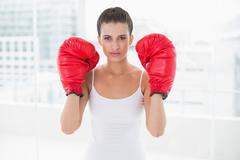 Stern natural brown haired woman in white sportswear wearing boxing gloves - stock photo