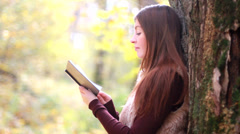 Beautiful girl with book in the autumn park Stock Footage