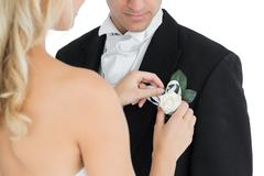 Blonde bride pinning a flower on the suit of her husband - stock photo