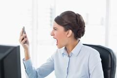 Angry classy brown haired businesswoman shouting at her mobile phone Stock Photos